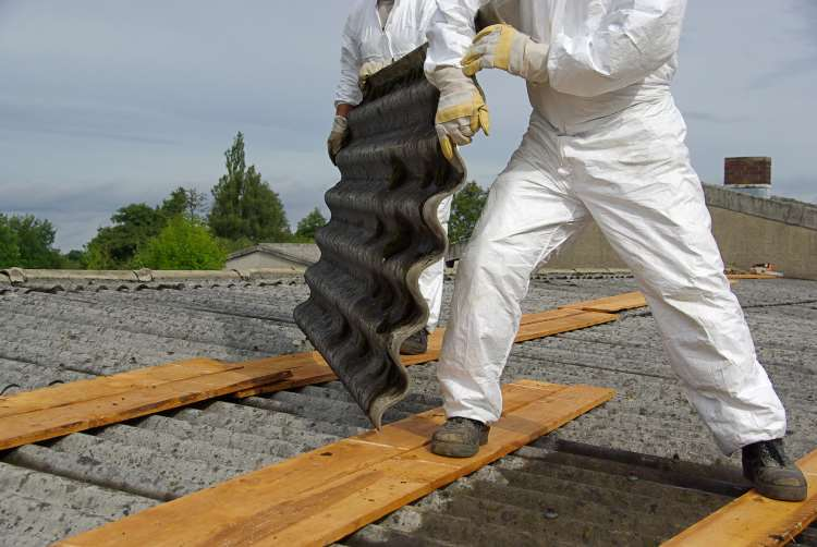 Image for persoanl injury asbestos claims compensation page - Man removing asbestos from roof in protective gear