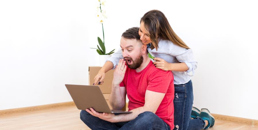 Image for Conveyancing Costs Calculator Plymouth Property Solicitors Page - Couple with laptop getting a Pleasantly surprising quote
