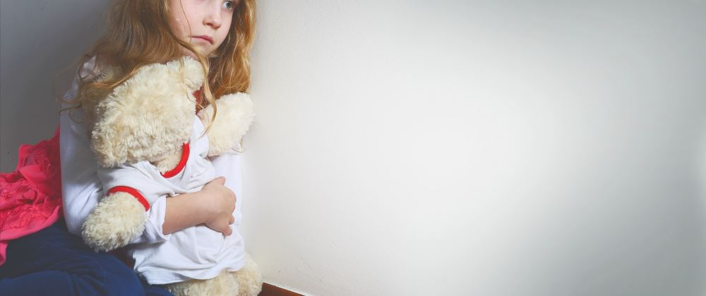 Plymouth Family Law Solicitor home page image of Frightened girl hugging a teddy bear